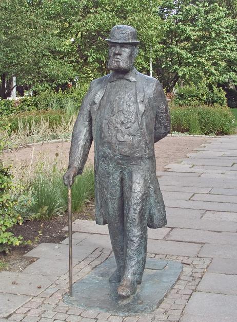 Staty av Charles Felix Lindberg. Han spatserar fram i hatt och käpp, med ena handen vilandes på ryggen.