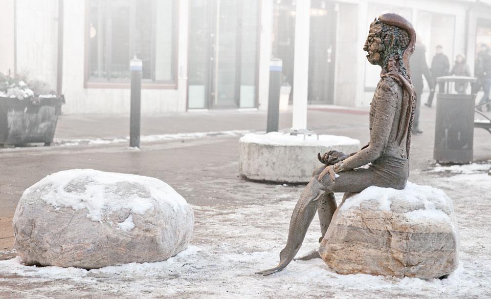 Vintertid. Oraklet sitter på en sten med en tom sten mittemot. På marken och stenarna ligger snö.