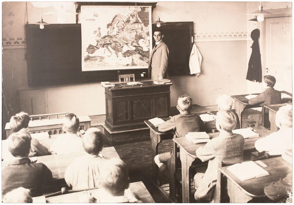 Bild på lärare och elever. Läraren pekar på en Europakarta