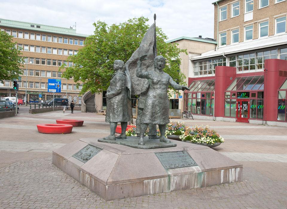 Skulpturgrupp bestående av en gravid kvinna, en kvinna som ropar och en man som bär en fana.
