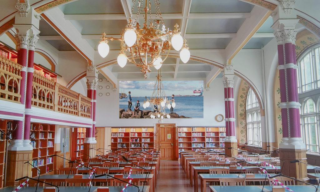 Visualiseringsbild av fotografiet när det hänger på kortsidan inne i Samhällsvetenskapliga bibliotekets pampiga läsesal.