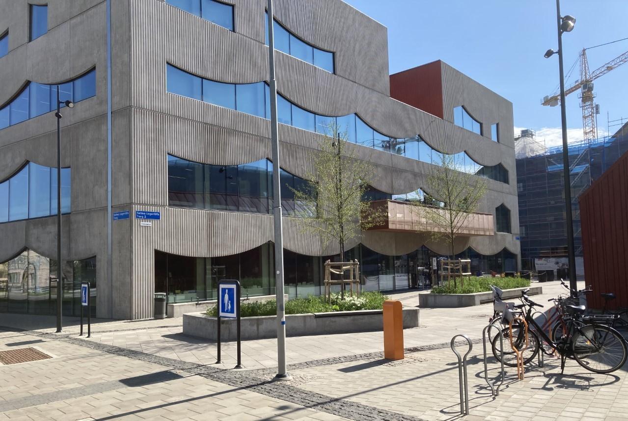 Selma Lagerlöfs Centers fasad pryds av ikoniska fönster i svängda former. Framför entrén syns två större rabatter.