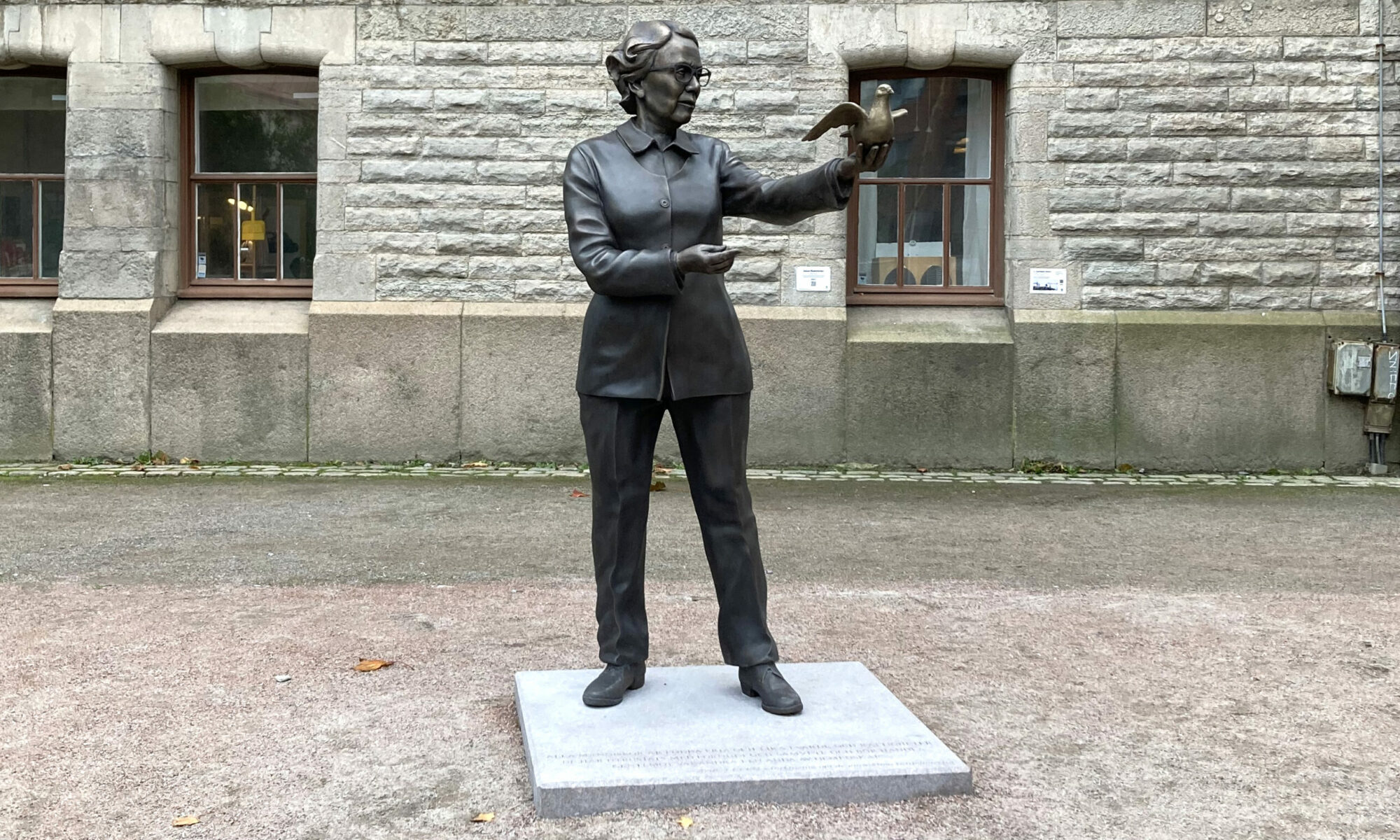 Skulptur av Ingrid Segerstedt Wiberg. Ena armen är utsträckt, och på den sitter en fredsduva som ser ut att vara redo att flyga iväg.
